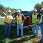 Four workers stand next to a truck by a road during an intelligent compaction demo project in Pennsylvania